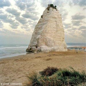 Gargano Vieste Scoglio Pizzomunno spiaggia con ombrelloni chiusi sullo sfondo e mare